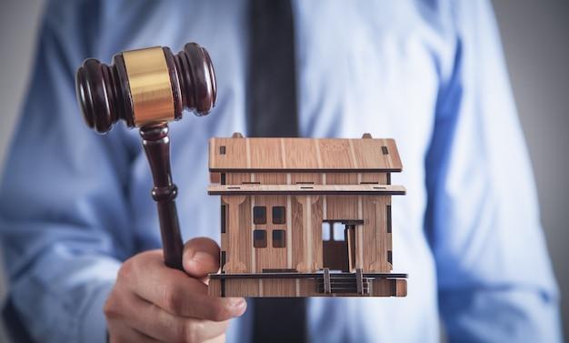 Мужчина держит деревянный дом и судья молотком