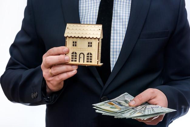 Мужчина держит модель деревянного дома и долларовые банкноты