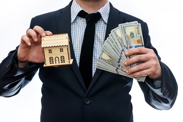 Man holding wooden house model and dollar banknotes