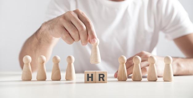 Человек, держащий деревянную человеческую фигуру. слово hr на деревянных кубиках. человеческие ресурсы