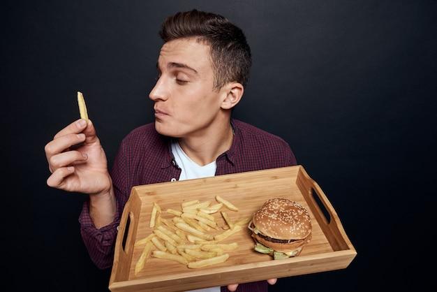 Мужчина держит в руках деревянный поддон с фаст-фудом, диетическое питание, голод, образ жизни, темный