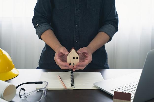 オフィスで木造の小さな家を持っている男