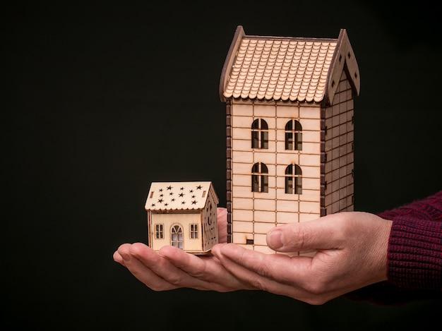 黒の背景に彼の手で木のおもちゃの家を保持している男