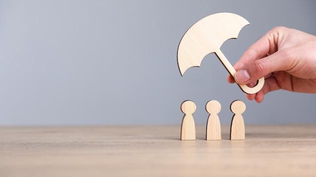 Человек, держащий деревянный зонтик и людей на столе