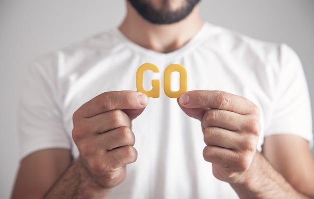 Мужчина держит деревянное слово go.