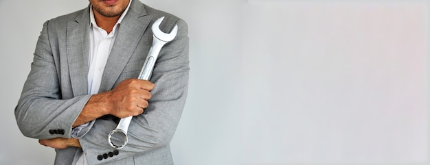 Man holding wrench on grey background with copy space.