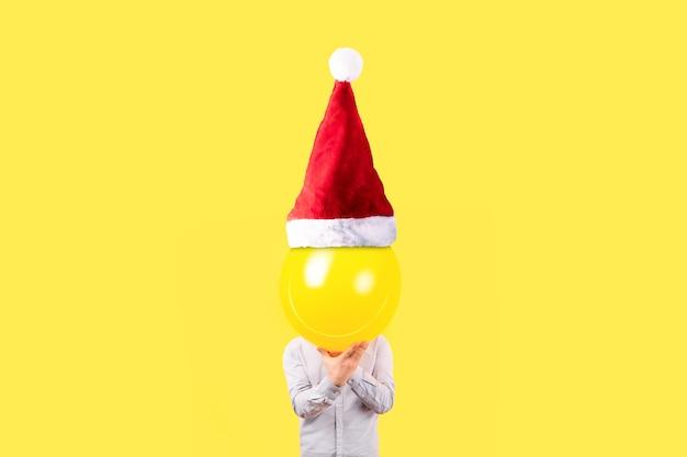 Мужчина держит желтый шар в шляпе санта-клауса