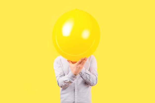 머리 대신 미소 얼굴 감정을 가진 노란 풍선을 들고 남자. 긍정적 사고 개념 프리미엄 사진