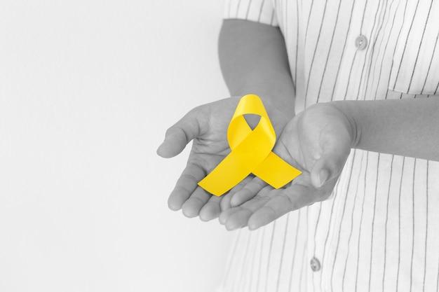 Мужчина держит желтую ленту