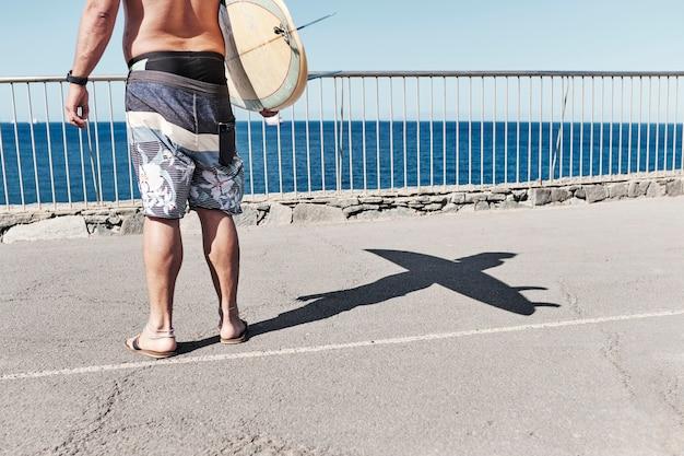 サニービーチの日に黄色のサーフボードを持って男