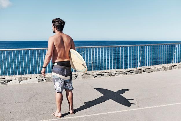 サニービーチで黄色のサーフボードを持って男