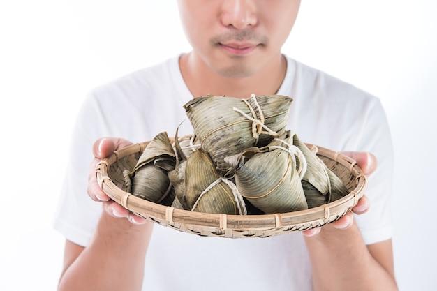 A man holding zongzi, rice dumpling for dragon boat festival