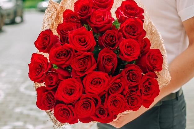 Мужчина держит букет красных роз для любимой