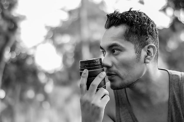 男はdsrlカメラレンズを持っています写真は白黒です