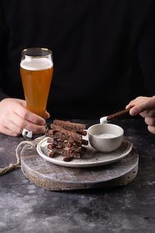 男はビールを片手にクルトンをガーリックソースで食べます。