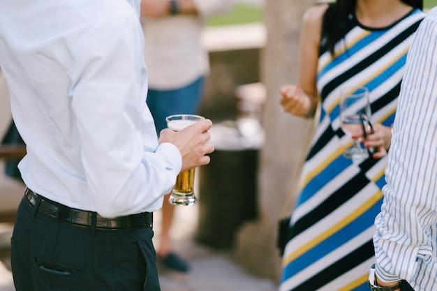 남자는 손에 맥주 한 잔을 들고 물 한 잔을 들고 있는 여자 옆에 서 있다