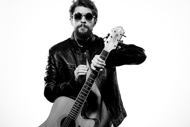 男は黒い革のジャケットを着て彼の手でギターを持っています
