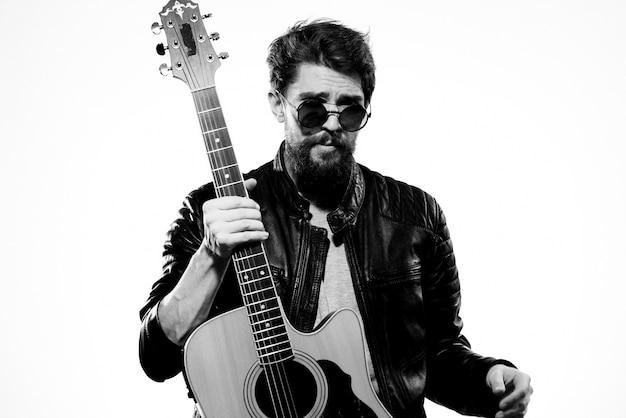Мужчина держит гитару в руках в черной кожаной куртке