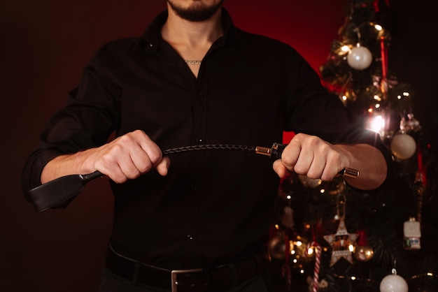 남자는 크리스마스 트리를 배경으로 지배와 복종을 위해 가죽 bdsm 채찍을 들고 있습니다. 휴가를위한 에로틱 한 선물의 아이디어