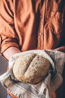 Мужчина держит буханку свежеиспеченного ржаного хлеба