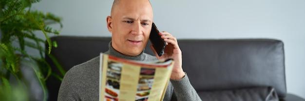 남자는 메뉴와 소파에서 휴대 전화에 대 한 얘기를 보유하고있다.