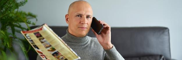 男はメニューを持ち、ソファで携帯電話で話している。