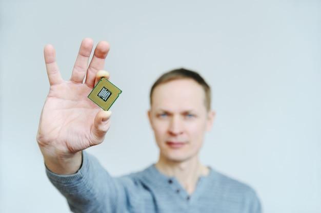 男は彼の指でマイクロチップを保持しています。