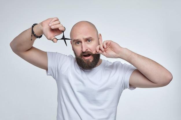 남자는 그의 콧수염을 자르려고 가위를 들고