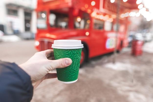 男はバスカフェの背景にコーヒーと紙コップを保持しています。