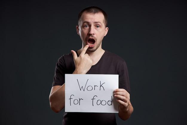 Мужчина держит в руках лист плаката с надписью «я работаю за еду». улыбка и радость, место для текста, копия пространства