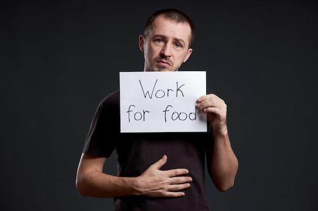 男は私が食べ物のために働いている碑文が書かれたポスターの紙を手に持っています。笑顔と喜び、テキストの場所、コピースペース