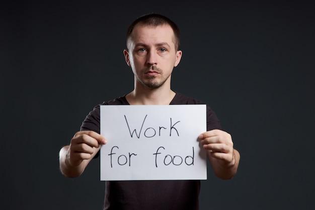 男は、私が食べ物のために働いているという碑文が書かれたポスターの紙を手に持っています。笑顔と喜び、テキストの場所、コピースペース