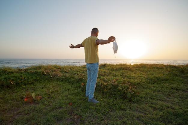 남자는 일출 때 바다 해안에 서 있는 손에 보호용 안면 마스크를 들고 있습니다.