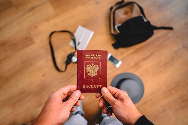 男はバックパックと旅行アクセサリーとロシアのパスポートを保持します
