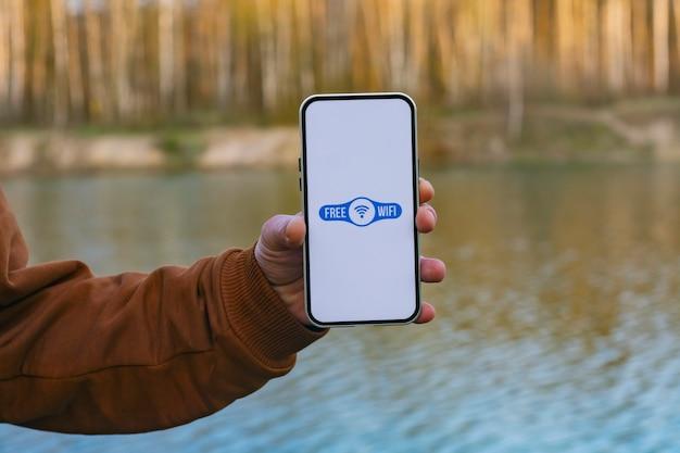男は、ディスプレイに無料のwi-fiアイコンが表示されたスマートフォンを手に持っています。森と湖の背景に電話。自然の中で無料のインターネットアクセス。