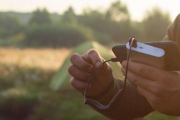 남자는 손에 스마트폰을 들고 자연의 관광 텐트를 배경으로 보조 배터리로 충전합니다. 휴대용 여행용 충전기.
