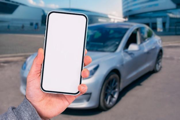 남자는 손에 스마트폰을 들고 있다. 자동차 배경에 흰색 화면이 있는 전화기를 조롱합니다.
