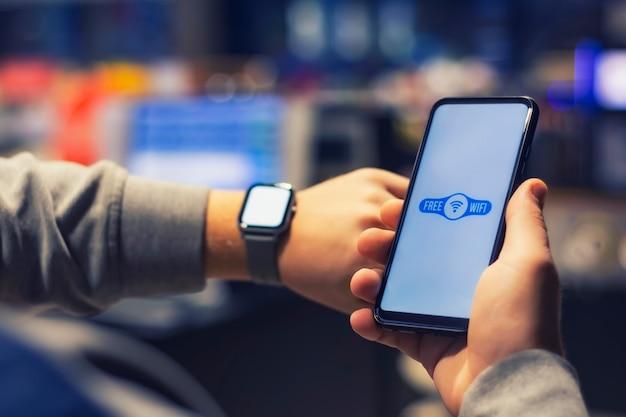 Мужчина держит смартфон со значком wi-fi крупным планом и умные часы в руке.