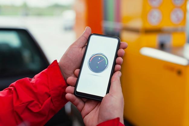 한 남자가 화면에 디지털 연료 미터가있는 스마트 폰을 들고