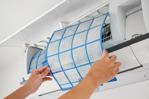 Man holds air conditioner filter