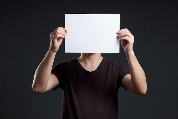 남자는 그의 손에 빈 포스터 종이 시트를 보유하고 있습니다. 미소와 기쁨, 텍스트 장소, 복사 공간