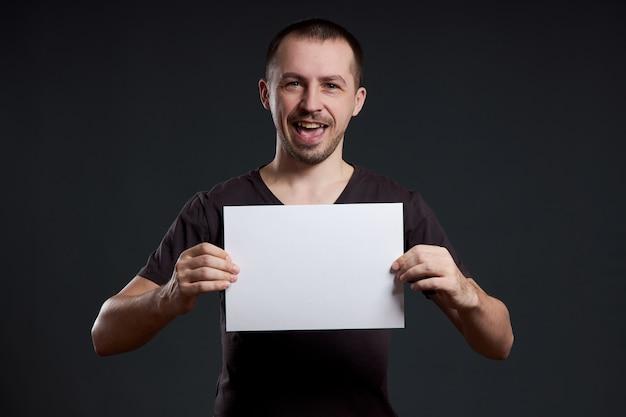 남자는 그의 손에 빈 포스터 종이 시트를 보유하고 있습니다.