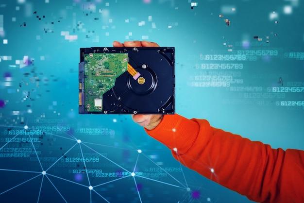 남자는 저장 및 메모리 청록색 배경의 하드 디스크 개념을 보유하고 있습니다.