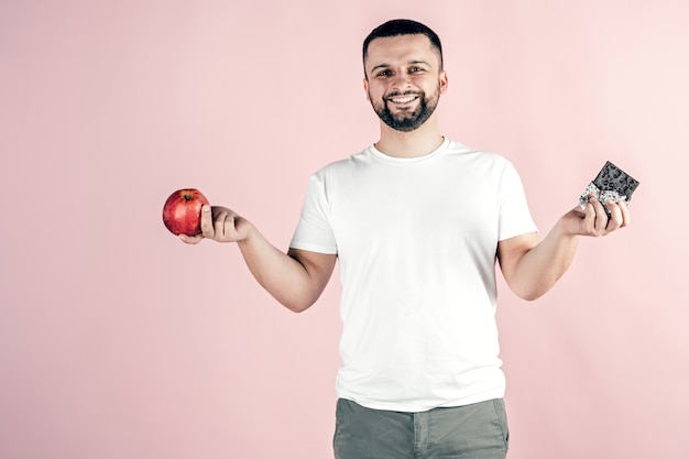 A man holds an apple and chocolate in his hands. healthy and unhealthy food.
