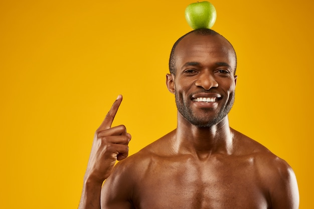 Man holds apple on top of head. green world concept.