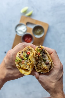 Man holds authentic mexican tacos with pork meat and vegetables