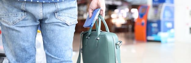 남자는 공항에 서 있는 동안 손에 여권과 티켓이 든 가방을 들고 있다