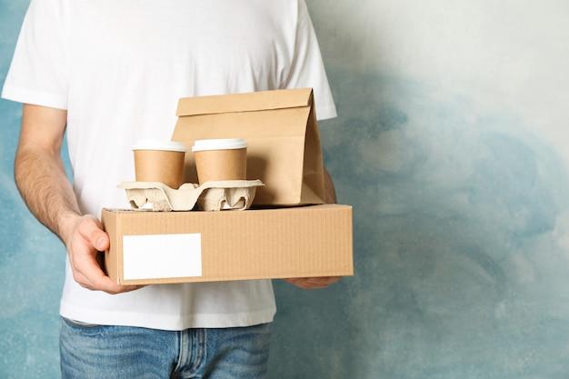 男は空白のボックス、コーヒーカップ、紙パッケージ屋内、テキスト用のスペースを保持しています。