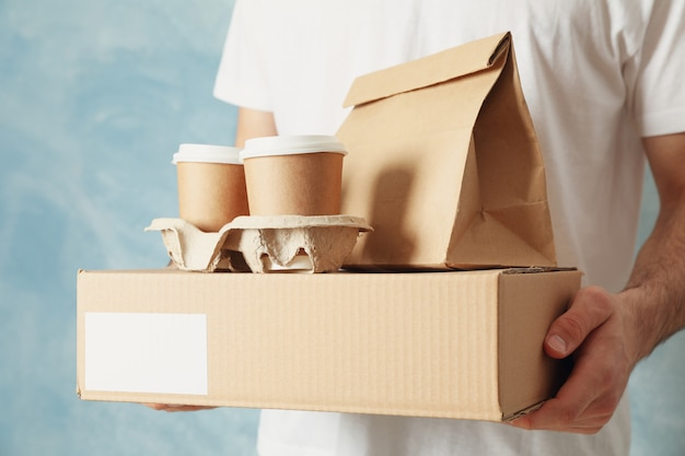 Man holds blank box, coffee cups and paper package indoor, space for text
