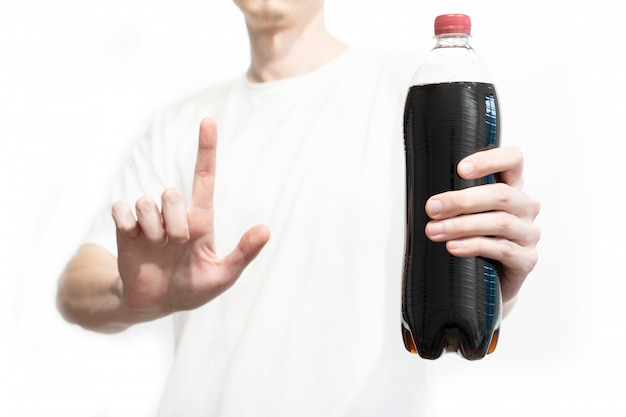Man holds a bottle of cola and showing attention sign by forefinger on white